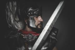 Puissance, légionnaire romain prétorien et manteau, armure et épée rouges Photo stock