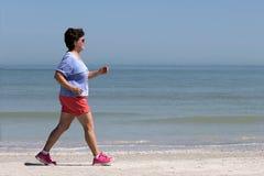Puissance supérieure de femme marchant sur une plage Photo libre de droits