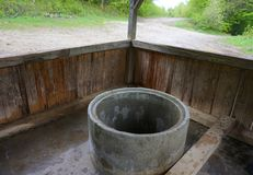 Puits concret pour l'eau sous un toit en bois images stock