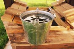 Puits d'eau et seau Photo stock
