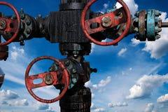 Puits de pétrole et de gaz avec le ciel bleu et les nuages blancs à l'arrière-plan photos stock