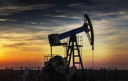 Puits de pétrole fonctionnant profilé sur le ciel de coucher du soleil Photos stock