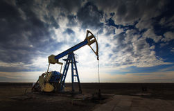 Puits de pétrole fonctionnant profilé sur le ciel nuageux excessif Photos stock