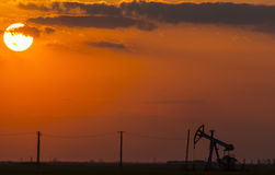 Puits fonctionnant de pétrole et de gaz profilé sur le ciel de coucher du soleil photographie stock libre de droits
