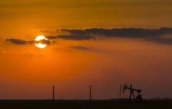 Puits fonctionnant de pétrole et de gaz profilé sur le ciel de coucher du soleil image stock