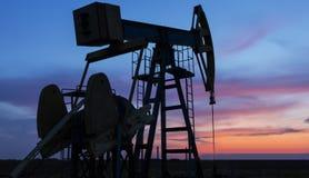 Puits fonctionnant de pétrole et de gaz profilé sur le ciel de coucher du soleil image libre de droits
