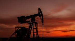 Puits fonctionnant de pétrole et de gaz profilé sur le ciel de coucher du soleil images libres de droits