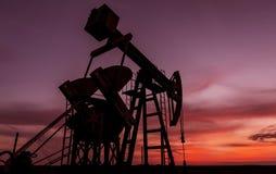 Puits fonctionnant de pétrole et de gaz profilé sur le ciel de coucher du soleil photo libre de droits