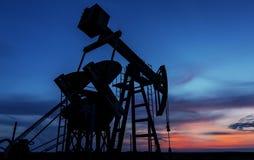 Puits fonctionnant de pétrole et de gaz profilé sur le ciel de coucher du soleil photos libres de droits