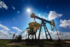Puits fonctionnant de pétrole et de gaz profilé sur le ciel ensoleillé Photographie stock libre de droits