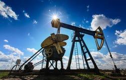 Puits fonctionnant de pétrole et de gaz profilé sur le ciel ensoleillé Images libres de droits