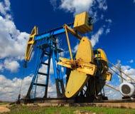 Puits fonctionnant de pétrole et de gaz profilé sur le ciel ensoleillé Image libre de droits
