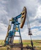 Puits fonctionnant de pétrole et de gaz profilé sur le ciel nuageux photos libres de droits