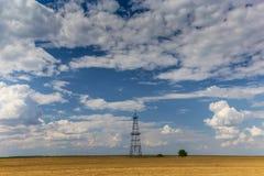 Puits fonctionnant de pétrole et de gaz profilé sur le ciel nuageux photographie stock libre de droits