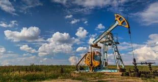 Puits fonctionnant de pétrole et de gaz profilé sur le ciel nuageux photographie stock