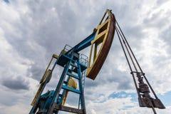 Puits fonctionnant de pétrole et de gaz profilé sur le ciel nuageux image stock