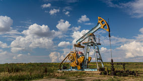 Puits fonctionnant de pétrole et de gaz profilé sur le ciel nuageux images libres de droits