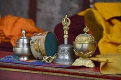 puja的礼节佛教对象:西藏响铃、一个鼓和银碗在喇嘛祷告桌上  免版税库存照片