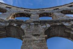 Pula, Croácia, arcos do anfiteatro contra o céu azul imagem de stock