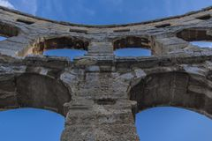 Pula, Croatia, arches of the amphitheater against blue sky stock image