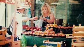 PULA, KROATIEN - 4. AUGUST 2017 Frau, die Pfirsiche am lokalen Markt verkauft Lizenzfreies Stockfoto