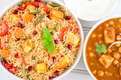 Pulao and Chole-Indian meal. A colorful Indian rice dish made from basmati rices, spices, and fresh vegetables served with chickpeas curry Cholle or channa Stock Images