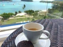 PULAU LANGKAWI, MALÁSIA - 4 de abril de 2015: Uma xícara de café e uma cookie na tabela com o mar no fundo Fotografia de Stock Royalty Free