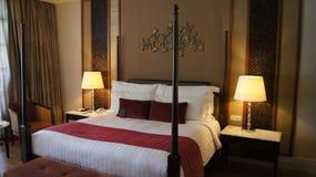 PULAU LANGKAWI, MALASIA - 4 de abril de 2015: Cama cómoda en una habitación de hotel de lujo en EL DANNA, diseño colonial del sit Foto de archivo