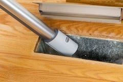 Pulendo dentro lo sfiato del pavimento del riscaldamento con l'aspirapolvere Fotografie Stock