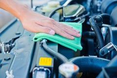 Pulendo il motore di automobile con il panno verde del microfiber Immagini Stock Libere da Diritti