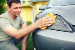 Pulendo l'automobile maschio sorridente automobilistica di pulizia con il panno del microfiber, automobile fotografia stock libera da diritti