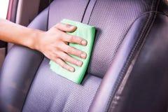 Pulendo l'interno dell'automobile con il panno verde del microfiber Fotografie Stock Libere da Diritti
