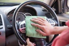 Pulendo l'interno dell'automobile con il panno verde del microfiber Fotografia Stock Libera da Diritti