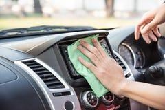Pulendo l'interno dell'automobile con il panno verde del microfiber Immagini Stock