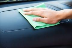 Pulendo l'interno dell'automobile con il panno verde del microfiber Immagine Stock