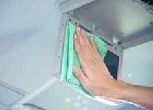 Pulendo l'interno dell'automobile con il panno verde del microfiber Immagini Stock Libere da Diritti
