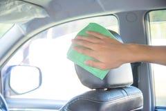 Pulendo l'interno dell'automobile con il panno verde del microfiber Fotografia Stock