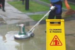 Pulendo nel simbolo bagnato del pavimento di cautela e di processo Immagini Stock