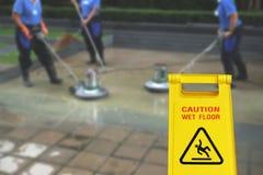 Pulendo nel simbolo bagnato del pavimento di cautela e di processo Immagini Stock Libere da Diritti