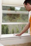 Pulendo un davanzale della finestra con un panno della polvere Fotografie Stock