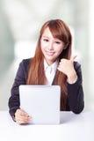 Pulgar de la demostración de la mujer de negocios encima de y usar la PC de la tableta imagen de archivo libre de regalías
