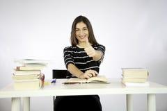 Pulgar de la muchacha para arriba mientras que estudia Foto de archivo libre de regalías