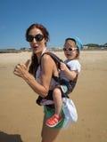 Pulgar del canto encima de la madre y del bebé en mochila Imagen de archivo libre de regalías
