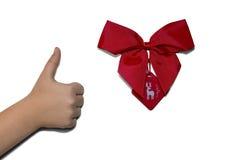 Pulgar del niño encima de la mano con la cinta roja Fotografía de archivo libre de regalías