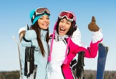 Pulgar en declive de dos de la hembra amigos del esquiador para arriba Imagen de archivo libre de regalías