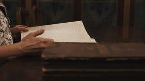Pulgar panorámico de la mujer mayor del tiro a través del texto cursivo ruso del libro en la tabla metrajes