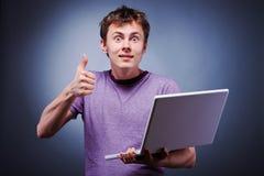Pulgar sorprendido de la sonrisa encima del hombre con la computadora portátil Foto de archivo libre de regalías