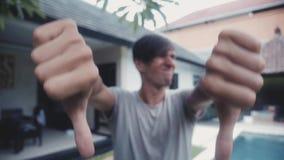 Pulgares abajo con ambas manos del hombre joven, en casa en el patio, al aire libre Concepto del desacuerdo metrajes