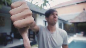 Pulgares abajo por el hombre joven, en casa en el patio, al aire libre Concepto del desacuerdo metrajes