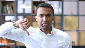 Pulgares abajo por el hombre negro en oficina Imagenes de archivo